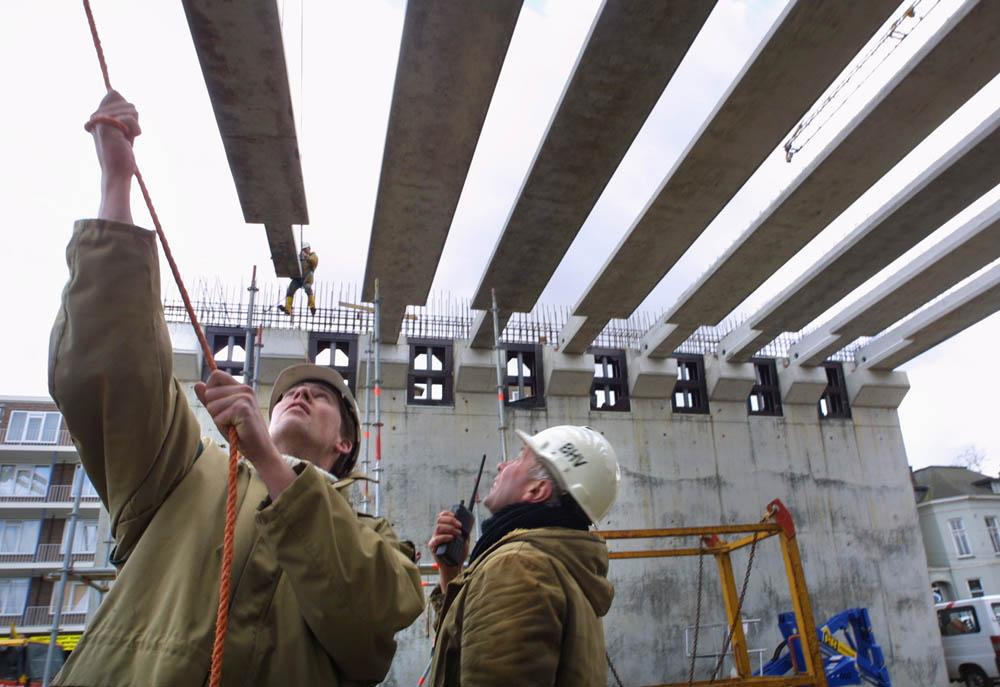 Arnhem, 260202 Ongeveer 150 liggers van 10.000 kg. per stuk worden in het stationgebied in Arnhem geplaatst. Bovenop de ondergrondse parkeergarage naast het station komt een nieuw overkapt busstation. De wanden hiervan staan er al, hierop worden liggers van Spanbeton uit Koudekerk aan de Rijn geplaatst. Op de liggers komt breedplaat waarop een betonnenvloer wordt gestort. Hier bovenop worden kantoren gebouwd. De werkzaamheden worden uitgevoerd door Aan de Stegge uit Arnhem. Foto: Sjef Prins - APA Foto VRIJBLIJVEND