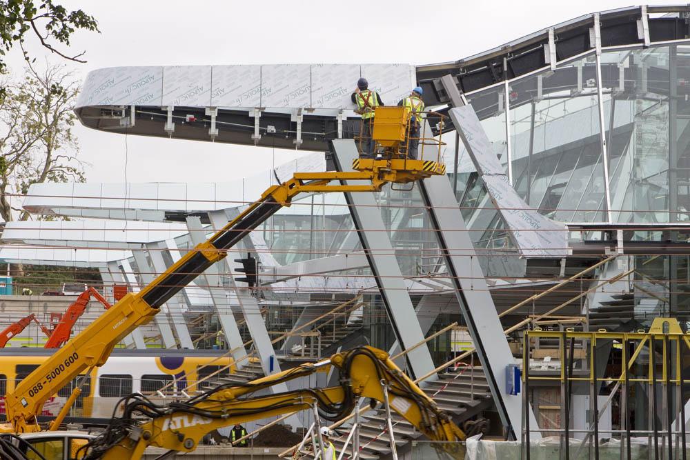 Futuristische passerelle in de maakARNHEM 200911 Het ziet er futuristisch uit, de nieuwe passerelle aan de noordzijde van station Arnhem Centraal. Sorba Projects bv uit Winterswijk bekleedt de gevels met Alpolics platen, deze composietplaten bestaan uit twee lagen met daartussen een harde onbrandbare kern, en worden ook gebruikt voor de nieuwe perronkappen. Hierdoor krijgt het hele station dezelfde uitstraling. De nieuwe brug maakt deel uit van het project Sporen in Arnhem en is straks de verbindende schakel tussen de Sonsbeek-entree en de verschillende perrons. Vanaf maandag gaat de passerelle open, maar is dan nog niet af. De binnenkant moet nog worden afgebouwd en dat zal in twee fases gebeuren. Telkens zal een zijde van de overgang afgesloten zijn, zodat passagiers via de andere kant nog naar de trein kunnen lopen. De nieuwe entree was nodig omdat ProRail het emplacement beter heeft ingericht, waardoor het aantal treinwissels met een derde afneemt. Hierdoor kunnen treinen sneller binnenkomen en vertrekken. De passerelle is naar verwachting eind 2011 klaar. WFA/bm/str. Sjef Prins